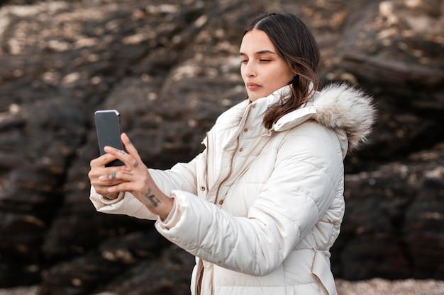 Vista lateral de mulher na praia tirando fotos com smartphone