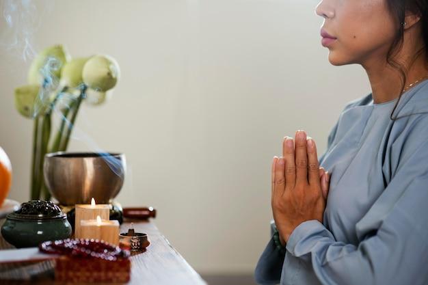 Vista lateral de mulher orando em frente a velas