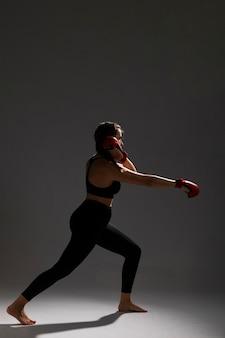 Vista lateral de mulher perfurando com luvas de caixa