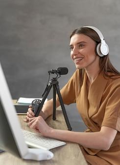Vista lateral de mulher podcasting com microfone e computador pessoal