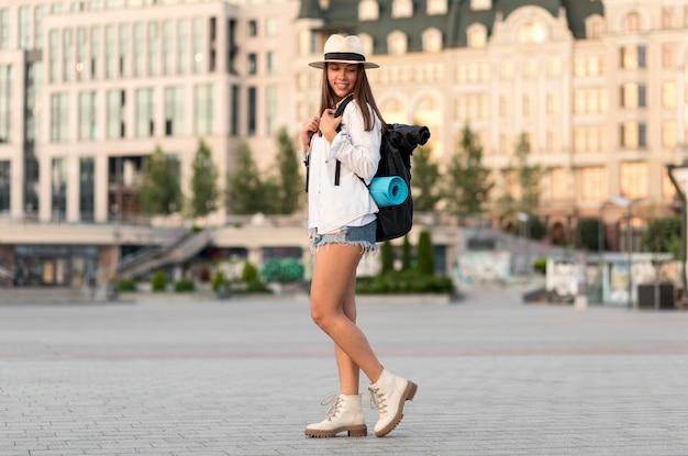Vista lateral de mulher posando enquanto viaja sozinha com uma mochila