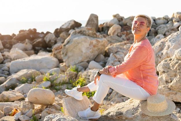 Vista lateral de mulher posando sobre pedras
