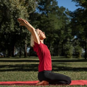 Vista lateral de mulher praticando posição de ioga ao ar livre