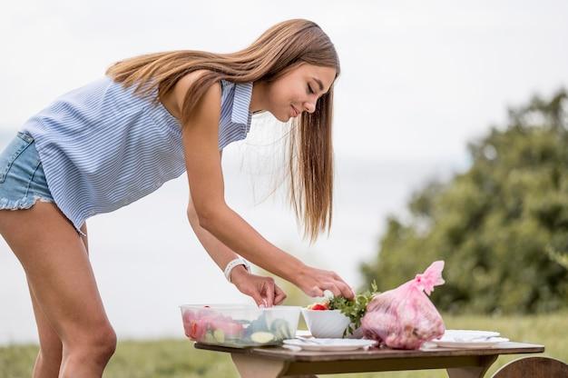 Vista lateral de mulher preparando comida para churrasco