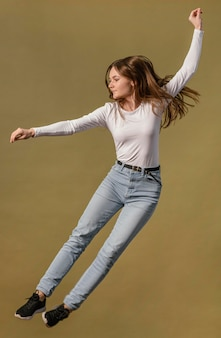 Vista lateral de mulher pulando no ar