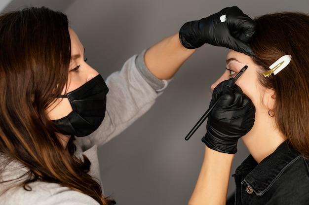 Vista lateral de mulher recebendo tratamento para sobrancelha com médico