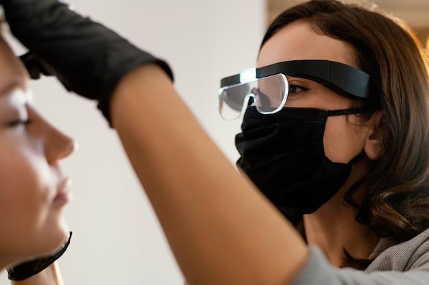 Vista lateral de mulher recebendo tratamento para sobrancelha por especialista