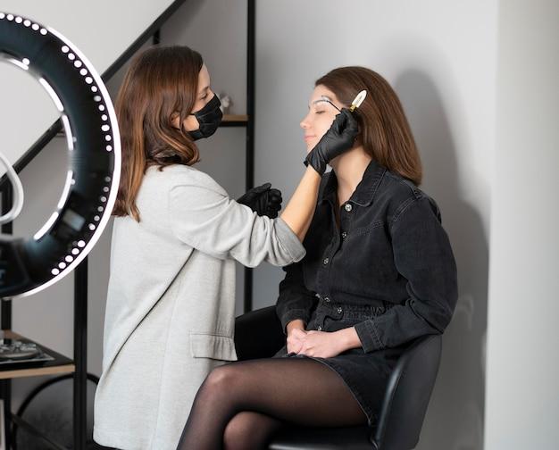 Vista lateral de mulher recebendo tratamento para sobrancelha