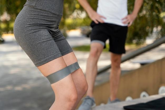 Vista lateral de mulher se exercitando ao ar livre com elástico