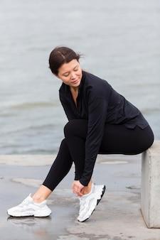 Vista lateral de mulher se exercitando ao ar livre com roupa ativa