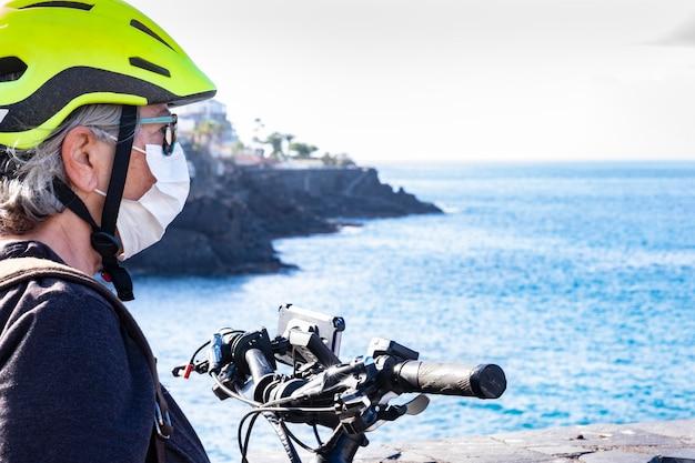 Vista lateral de mulher sênior desportiva com bicicleta elétrica. capacete amarelo para bicicleta - usa máscara médica para evitar infecção por coronavírus. horizonte sobre a água do mar