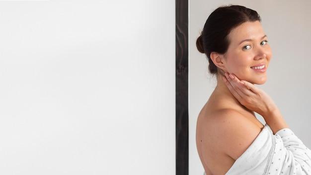Vista lateral de mulher sorridente em roupão de banho após autocuidado