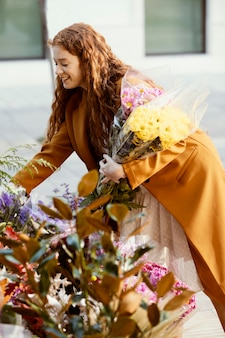 Vista lateral de mulher sorridente escolhendo buquê de flores de primavera