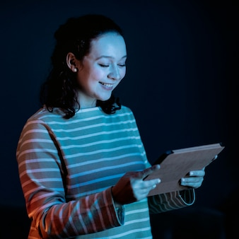 Vista lateral de mulher sorridente usando tablet