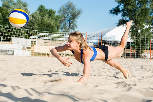 Vista lateral de mulher tentando jogar vôlei antes que ela atinja a areia