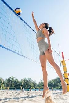 Vista lateral de mulher tentando pegar a bola sobre a rede enquanto joga vôlei de praia