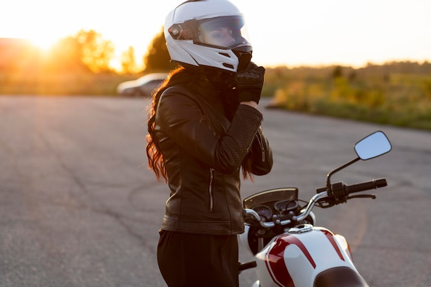 Vista lateral de mulher tirando o capacete ao lado da motocicleta