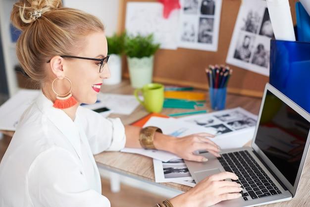 Vista lateral de mulher trabalhando com laptop em casa