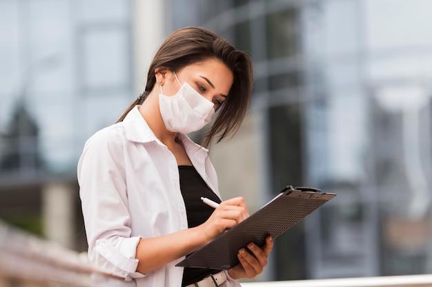 Vista lateral de mulher trabalhando durante a pandemia ao ar livre com o bloco de notas