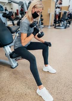 Vista lateral de mulher treinando máscara médica na academia