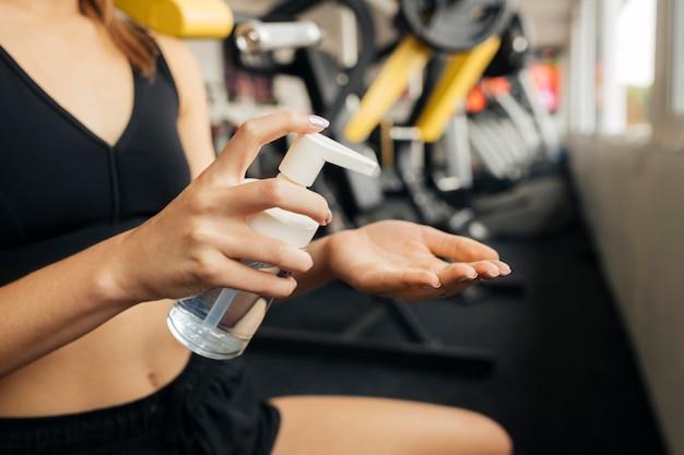Vista lateral de mulher usando desinfetante para as mãos na academia