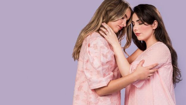 Vista lateral de mulheres abraçadas