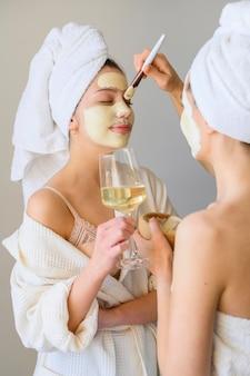 Vista lateral de mulheres aplicando máscaras em casa