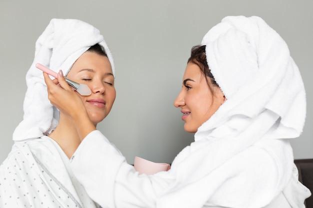 Vista lateral de mulheres aplicando produtos para a pele