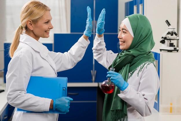 Vista lateral de mulheres cientistas no laboratório cumprimentando uns aos outros