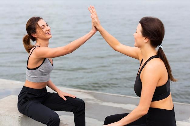 Vista lateral de mulheres cumprimentando-se enquanto se exercitam ao ar livre