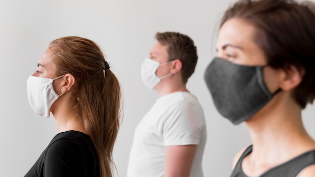Vista lateral de mulheres e homem com máscaras