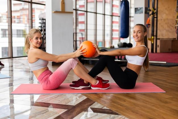 Vista lateral de mulheres exercitando na academia