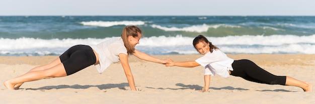 Vista lateral de mulheres fazendo flexões na praia