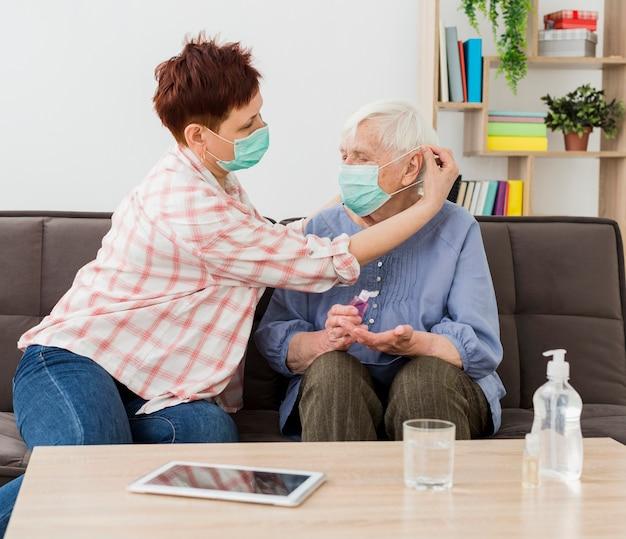 Vista lateral de mulheres mais velhas em casa usando máscaras médicas
