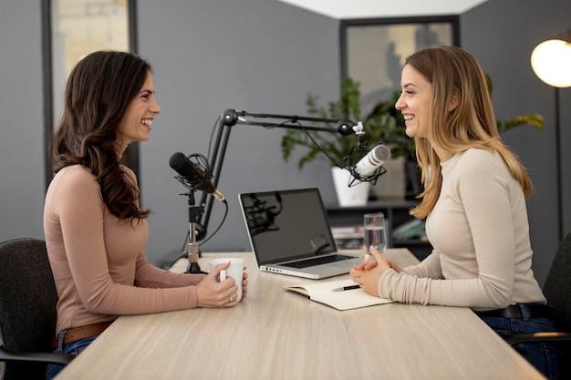 Vista lateral de mulheres no estúdio durante um programa de rádio