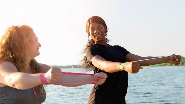 Vista lateral de mulheres se exercitando com elásticos à beira do lago