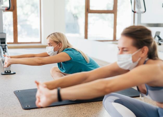 Vista lateral de mulheres se exercitando na academia durante a pandemia