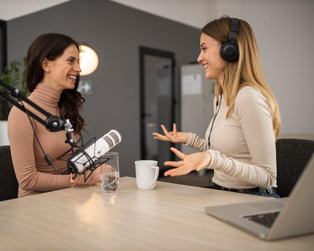 Vista lateral de mulheres sorridentes fazendo rádio juntas