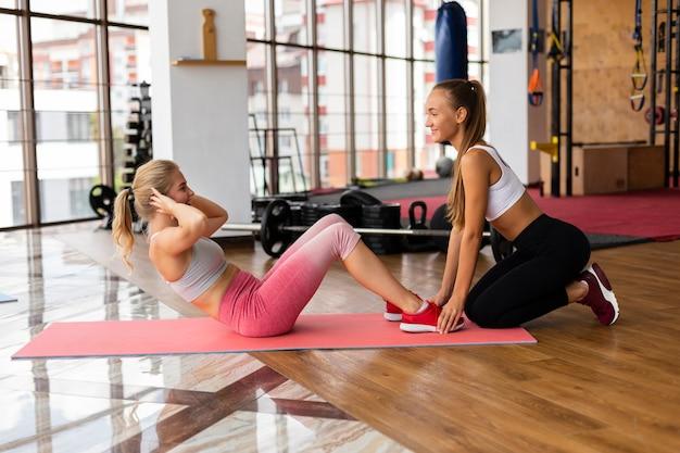 Vista lateral de mulheres treinando na academia