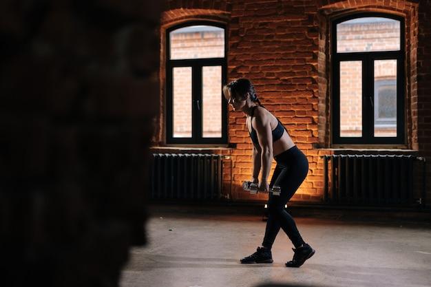 Vista lateral de musculoso jovem mulher atlética com belo corpo forte, vestindo roupas esportivas, levantando halteres. treino feminino de fitness caucasiano fora exercitando-se no ginásio escuro.