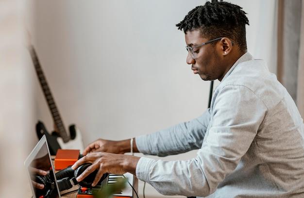 Vista lateral de músico masculino em casa mixando música com laptop