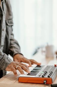 Vista lateral de músico masculino em casa tocando teclado elétrico