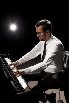Vista lateral de músico tocando piano