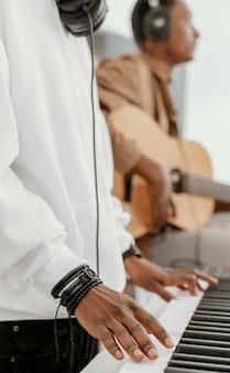 Vista lateral de músicos masculinos em casa tocando violão e teclado elétrico