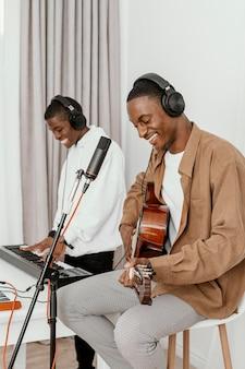 Vista lateral de músicos masculinos sorridentes em casa tocando violão e cantando