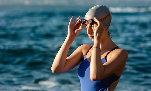 Vista lateral de nadadora com óculos de natação e boné