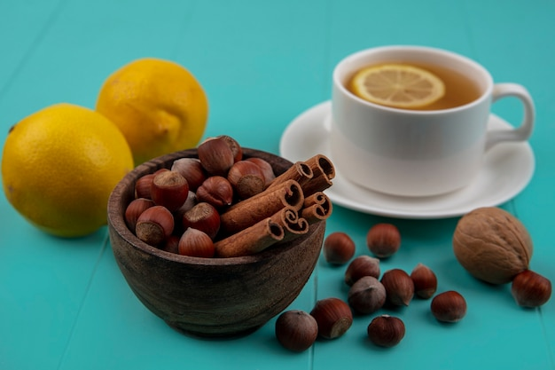 Vista lateral de nozes e canela em uma tigela com limões e uma xícara de chá no fundo azul