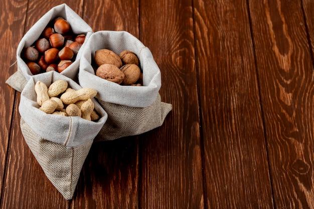 Vista lateral de nozes em sacos nozes amendoins e avelãs com casca em fundo de madeira