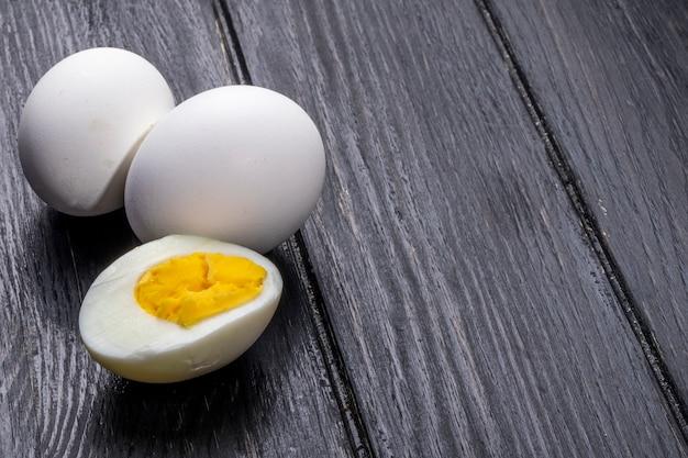 Vista lateral de ovos cozidos em madeira rústica