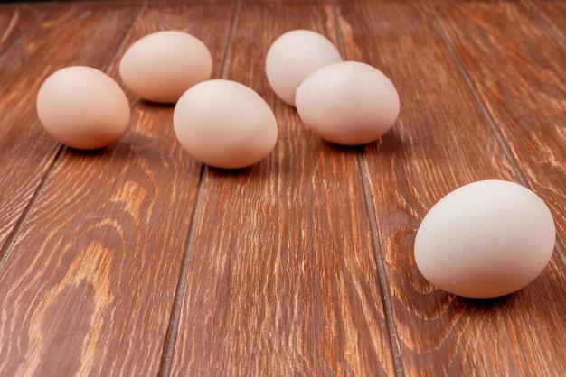 Vista lateral de ovos de galinha fresca, isolados em um fundo de madeira